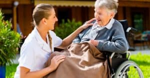 Aged care support worker caring for an elderly woman in a wheelchair.