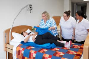 A trainer demonstrates manual handling techniques for Certificate III in individual Support course at Centacare.