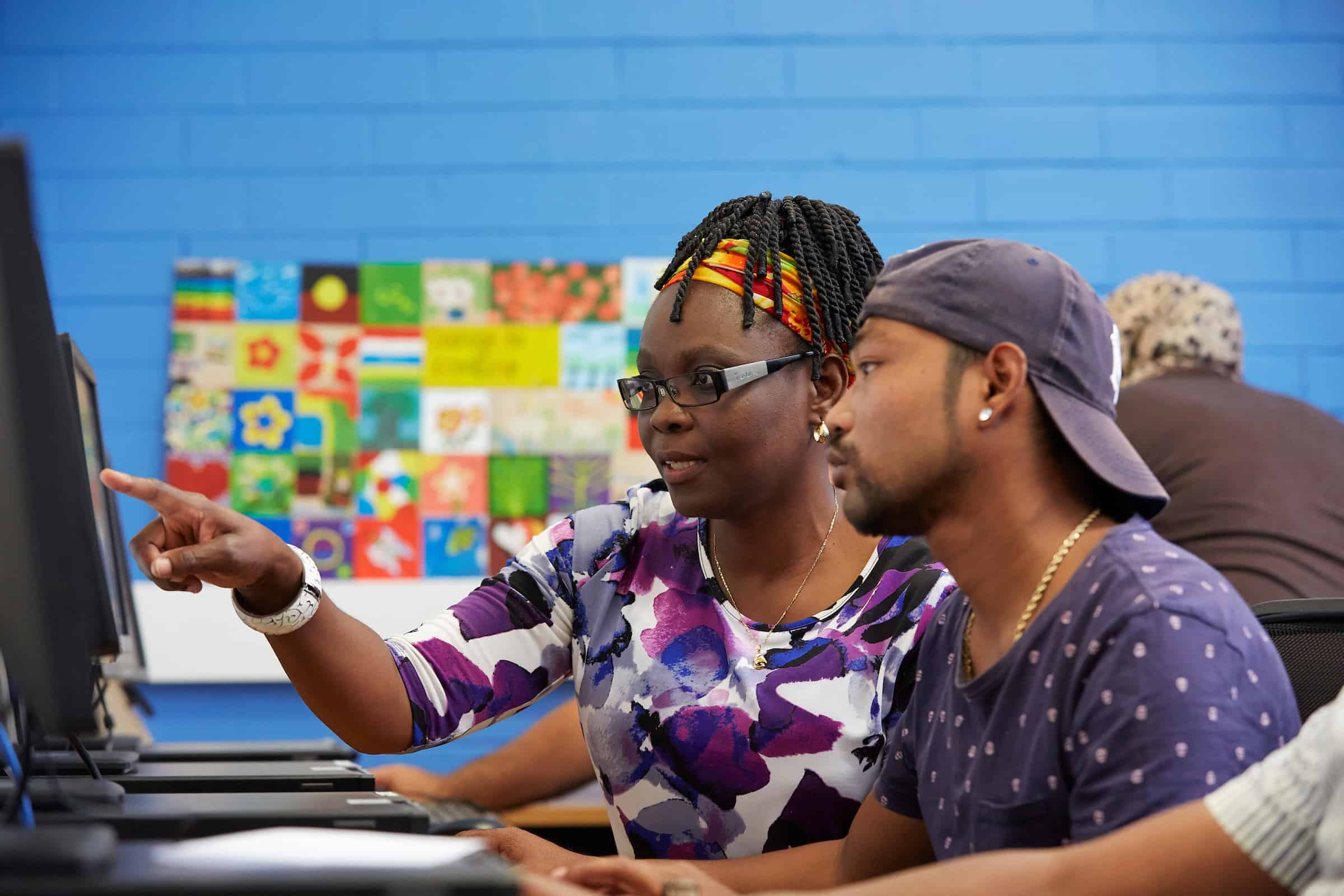 SEE teacher supporting a student on a computer at Centacare Cannington.