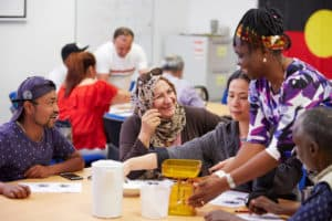 SEE teacher helps multicultural students with a group activity in a classroom at Centacare Cannington.