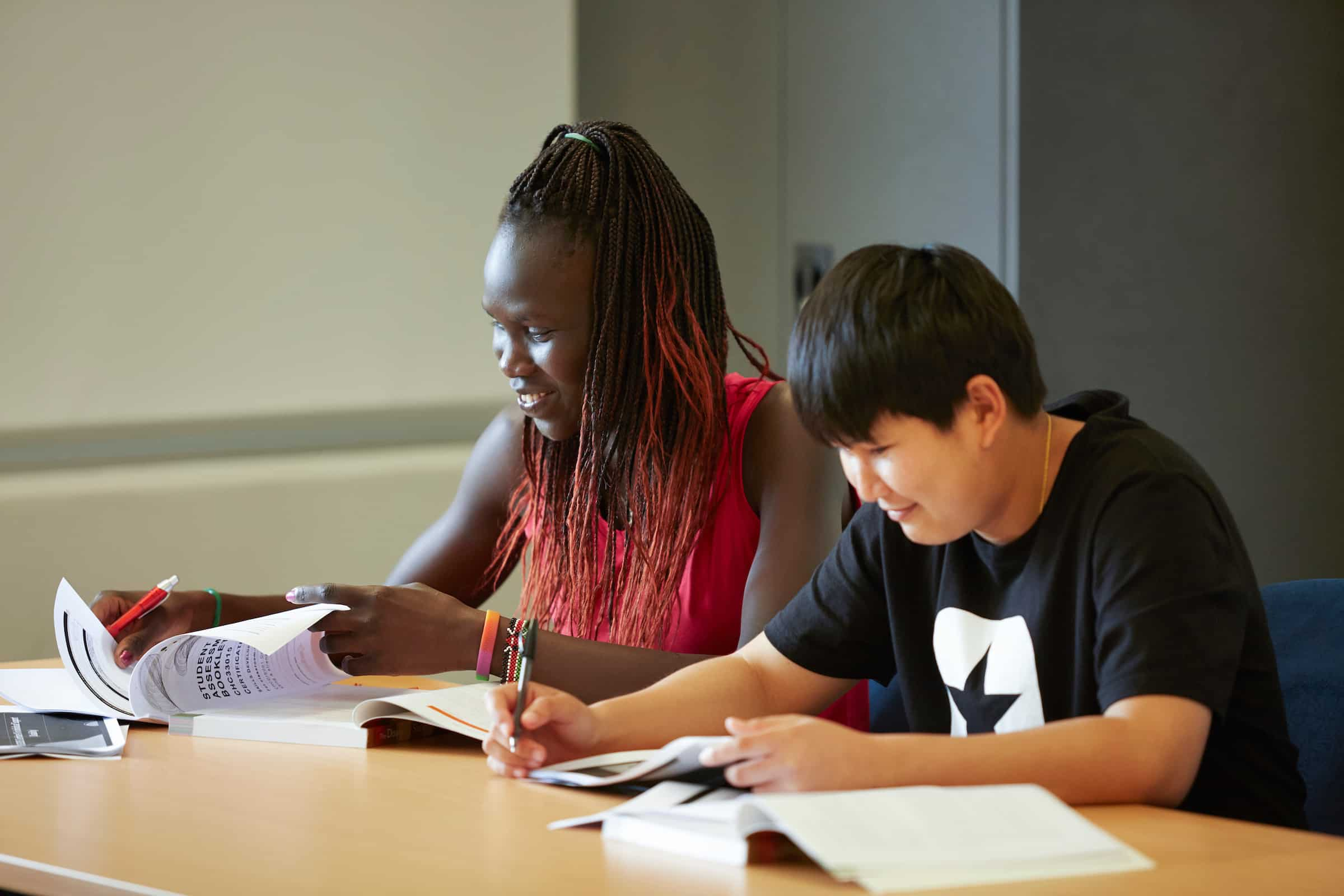 Two young multicultural students studying in a classroom at Centacare West Perth.