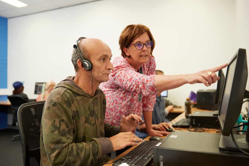 Teacher helping mature-aged male student at a computer.