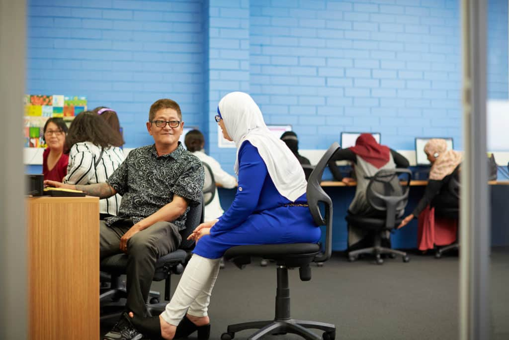 SEE teacher supporting mature-aged student in a computer lab at Centacare Cannington.