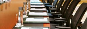 A line of folders and water in a Board meeting.