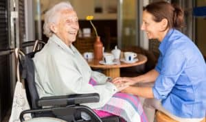 Senior woman in a wheelchair with aged care support worker.