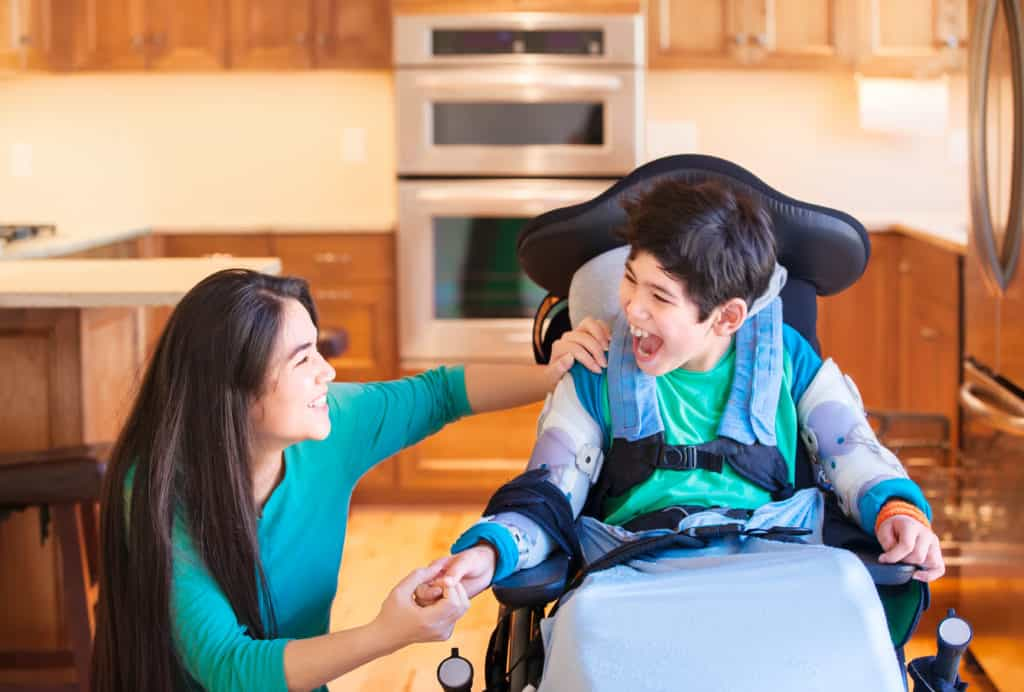 Disabled boy in wheelchair laughing with his disability support worker in a kitchen.