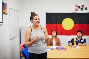Young Aboriginal woman participating in the Skills for Education and Employment (SEE) program presents to her class about Indigenous culture in Australia.